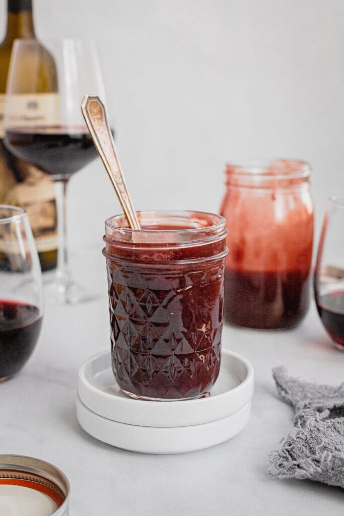 A glass mason jar full of homemade red wine caramel sauce. The jar has an antique spoon in it.