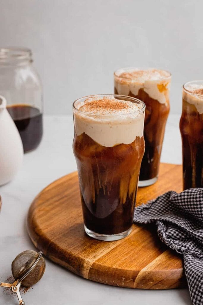 A pint glass sits on a wooden serving board. It is filled with homemade Irish cream cold foam and topped with a sprinkling of cocoa powder.
