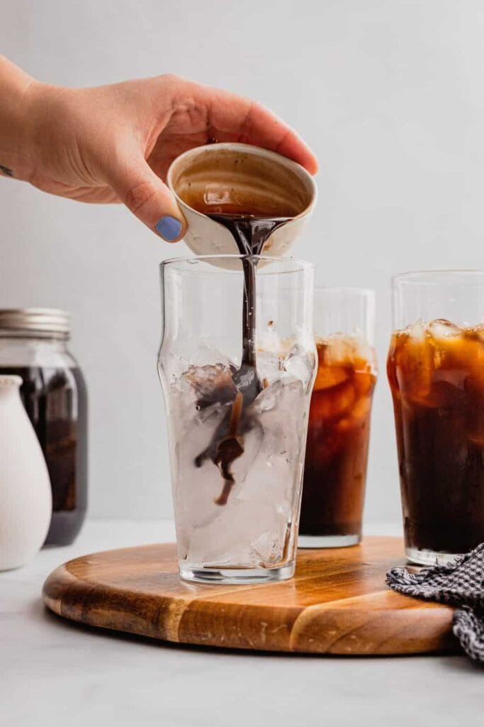 A hand pours a shot of Irish cream simple syrup into a glass filled with ice.