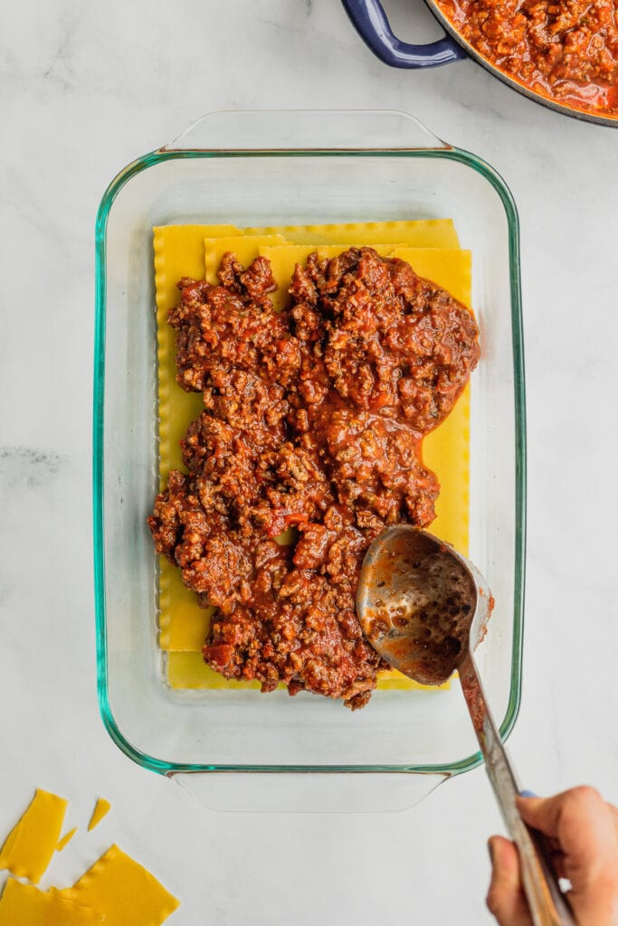 The first layer of meat sauce is added to a pan of mom's lasagna recipe.