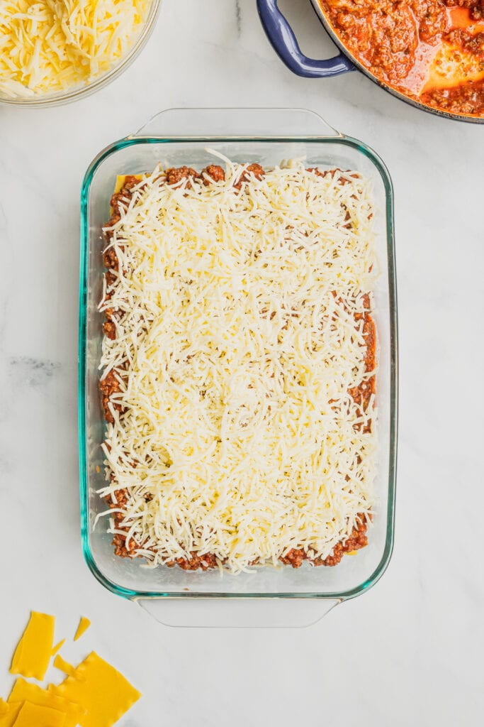 The second layer of shredded mozzarella cheese is added to a pan of homemade lasagna.