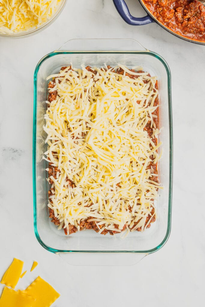 The first layer of shredded mozzarella cheese is added to the pan for homemade lasagna.