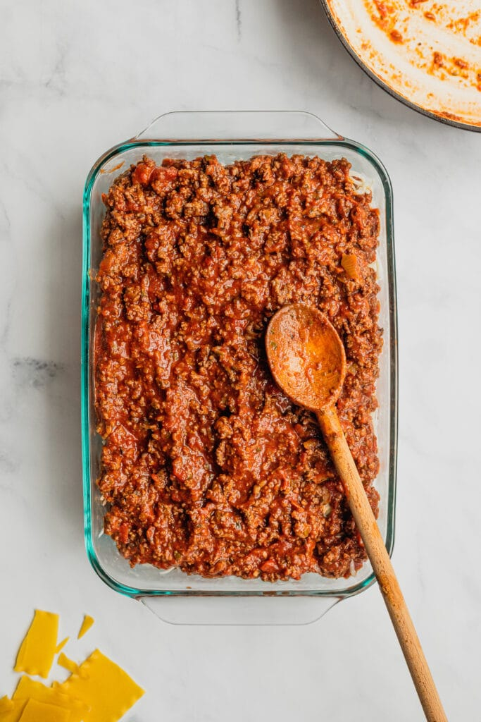 The third layer of meat sauce is added to a pan of homemade lasagna.