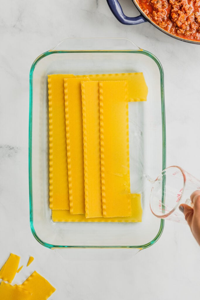 Water is poured under the first layer of noodles for a pan of lasagna.