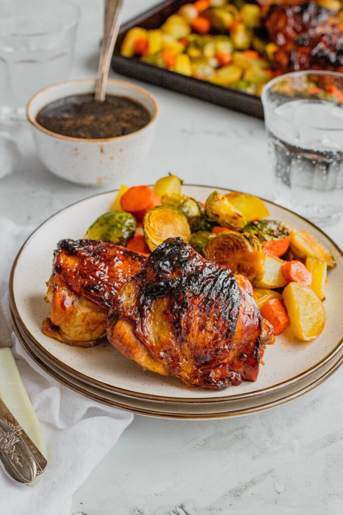 A plate filled with honey balsamic chicken thighs and roasted vegetables.