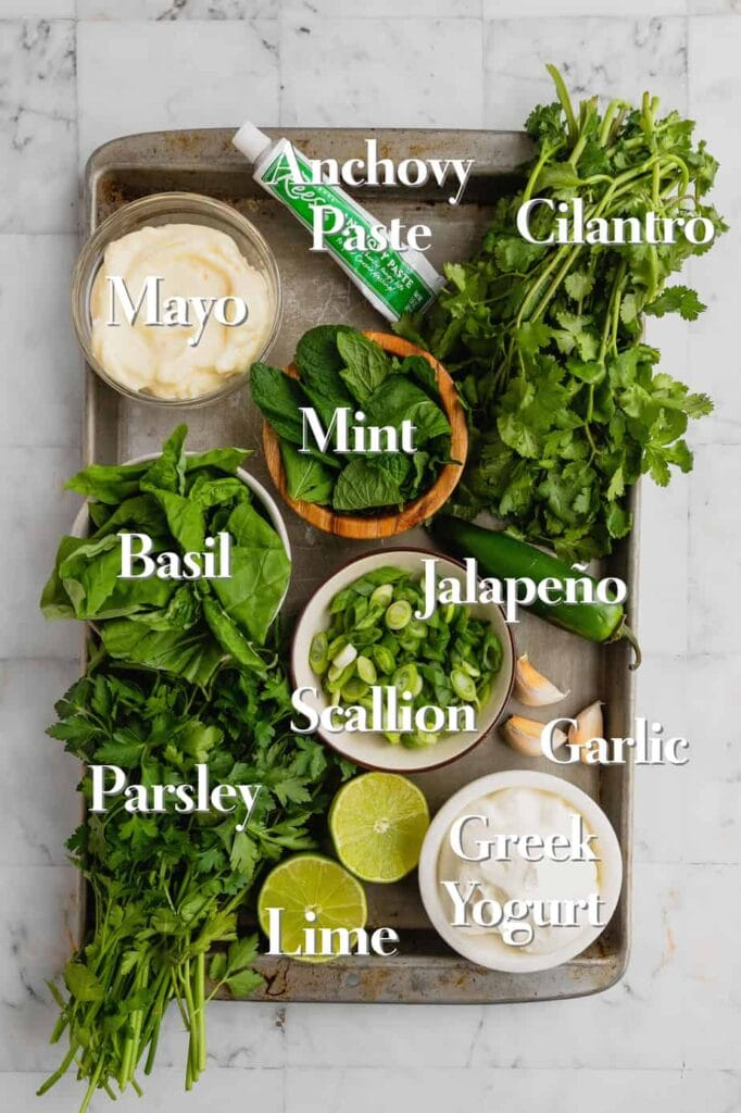 All of the ingredients for a green goddess dip recipe are on a metal tray in various bowls and bunches.
