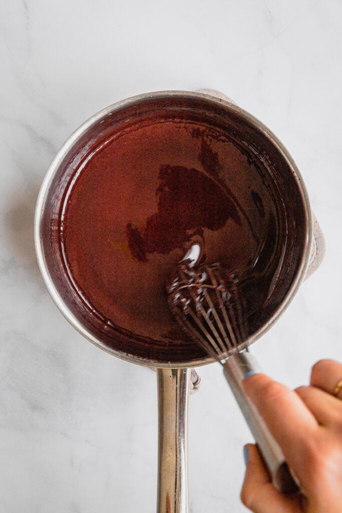A sauce pot full of smooth red wine caramel sauce.