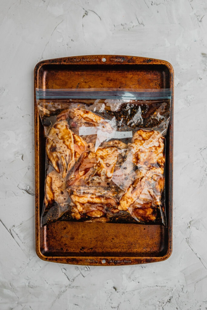 Chicken thighs in a zip-top plastic bag full of honey balsamic marinade on a baking tray.