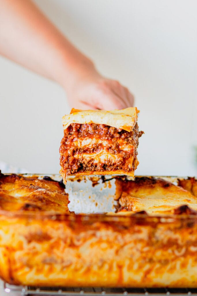 A close up of a perfect piece of lasagna being pulled from a pan.