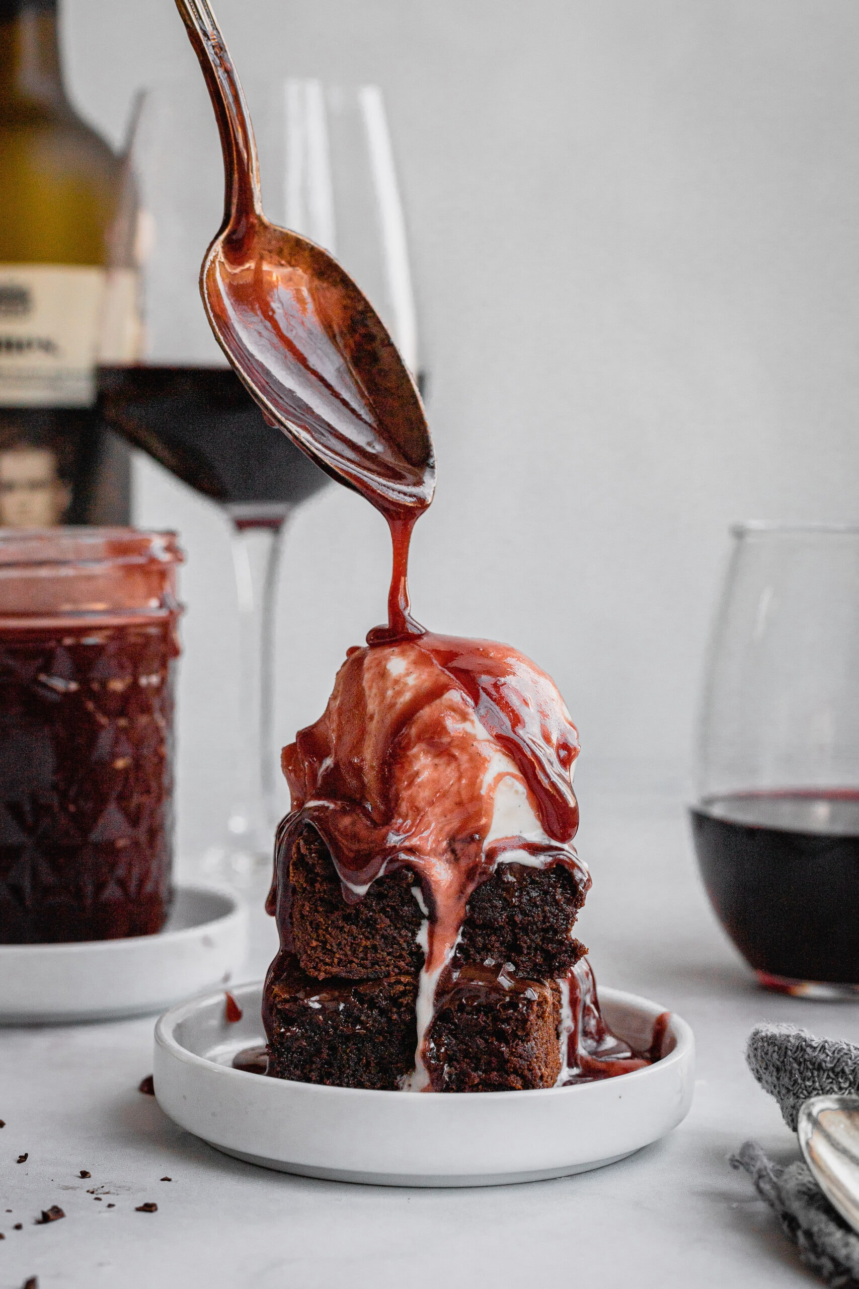 A spoon drizzles red wine caramel sauce onto a brownie a la mode.