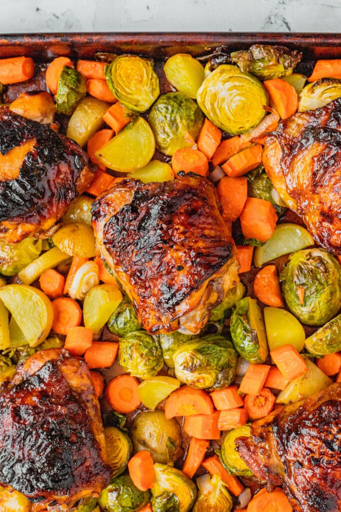 Honey balsamic chicken thighs on top of roasted vegetables.