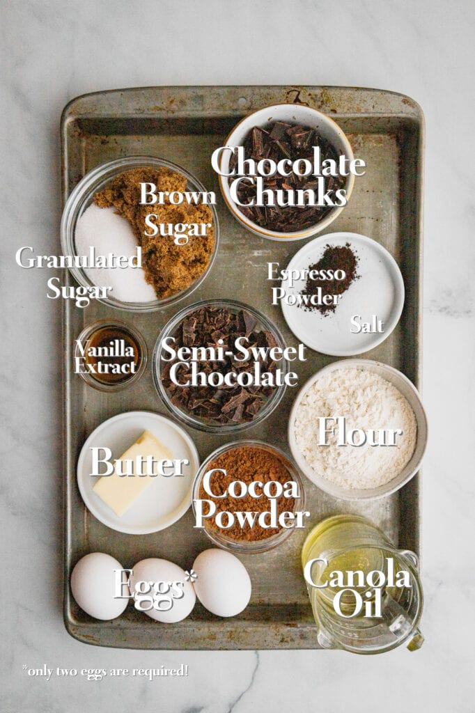 All the ingredients for triple chocolate brownies are on a baking tray in various glass bowls and measuring cups.