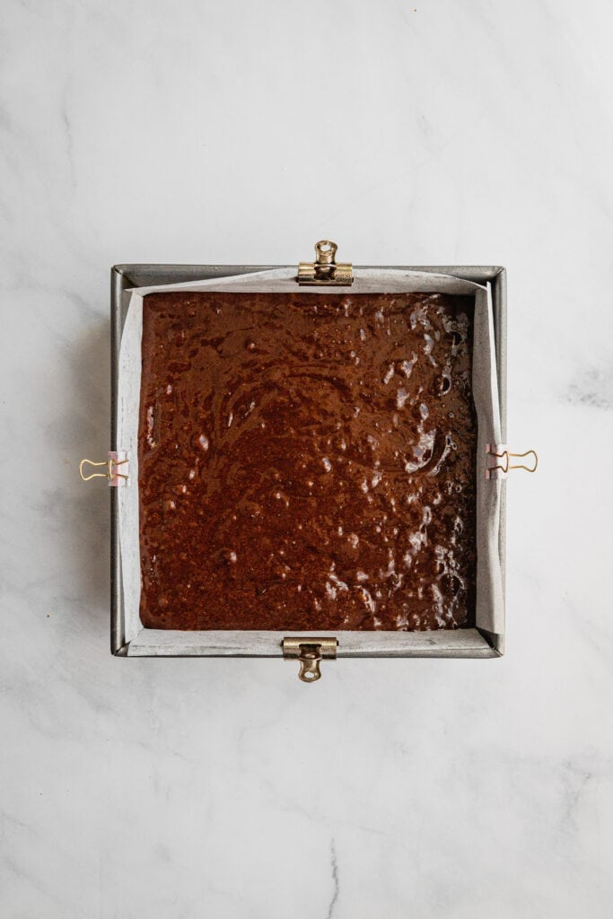 An 8x8 pan filled line with parchment paper and filled with brownie batter.