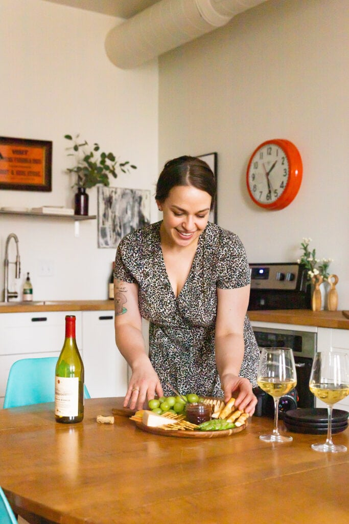 Food photographer and videographer Amanda Gajdosik smiles as she sets up a cheeseboard on a kitchen table. She is wearing a leopard print dress and her hair is pulled back.