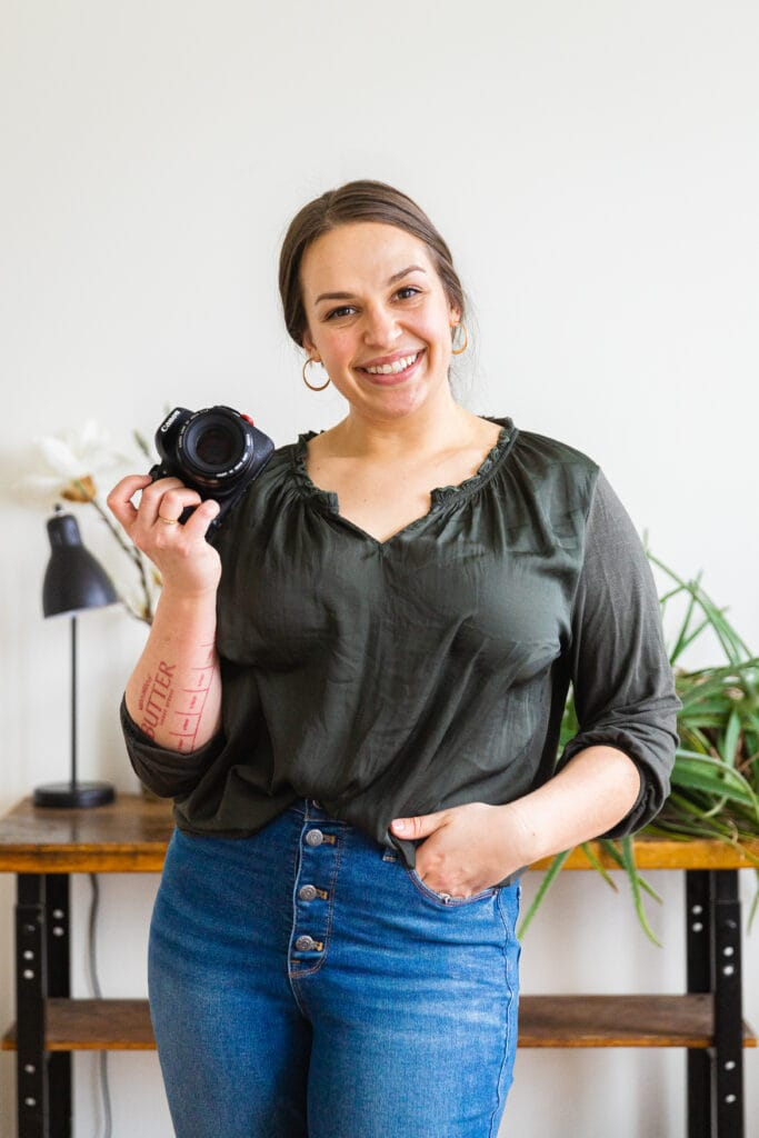 Amanda Gajdosik, a food writer and photographer, holds a camera while smiling. She is wearing a green top and jeans and her hair is pulled back.
