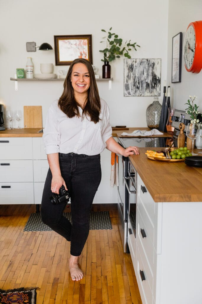 Amanda Gajdosik, food photographer and recipe developer, stands next to a kitchen counter. She is wearing a white shirt and black pants and holding her DSLR camera.