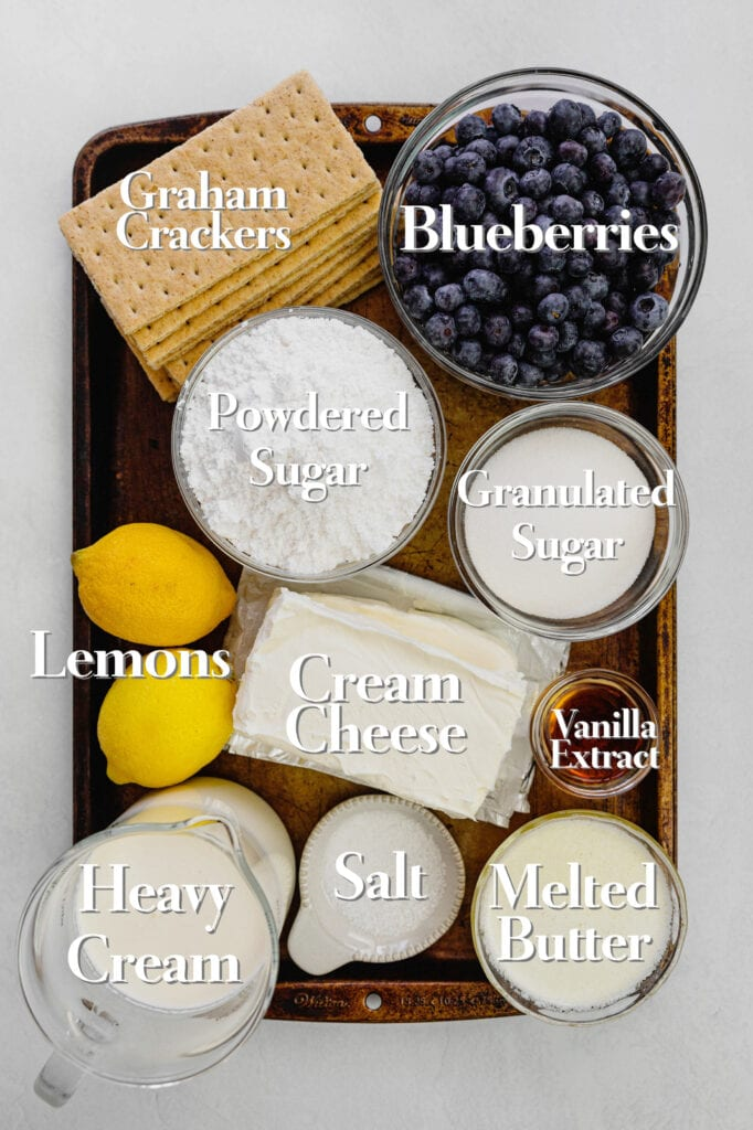 All of the ingredients for a simple no-bake cheesecake recipe with lemon and blueberry are in various glass bowls and measuring cups on a rimmed baking tray.
