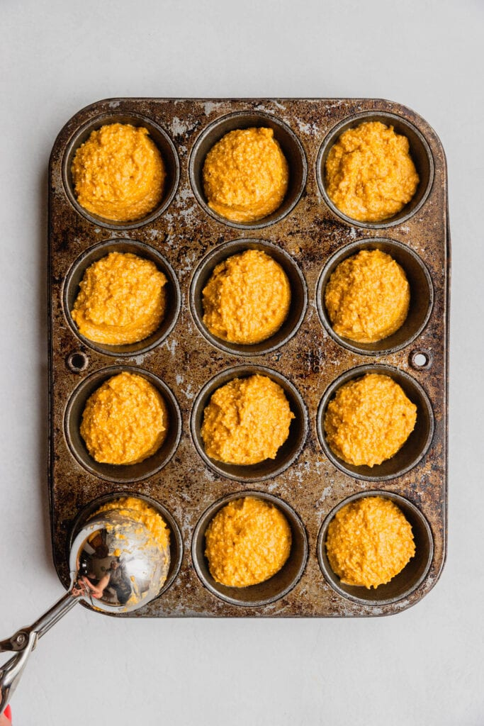 A muffin pan is filled with batter for homemade pupcakes.