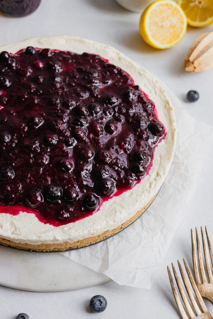 A no-bake lemon cheesecake covered in fresh blueberry sauce sits on a piece of parchment paper on a serving platter.