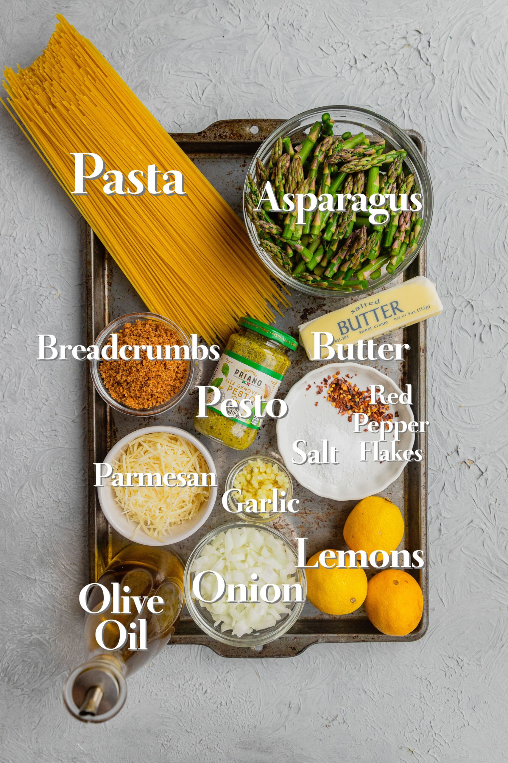All the ingredients for an asparagus pasta recipe are in various bowls on a rimmed baking sheet.