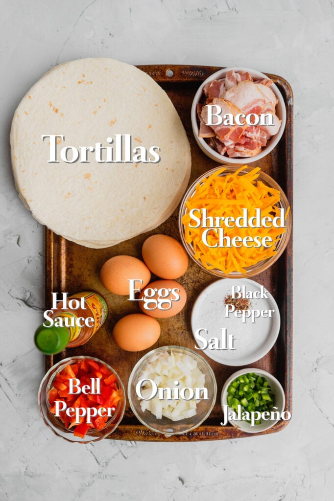 The ingredients for simple breakfast quesadillas are on a rimmed baking tray in various bowls.
