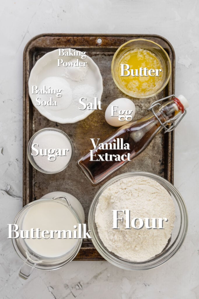 All the ingredients for homemade buttermilk pancakes are in various glass bowls and measuring cups on a rimmed baking sheet.