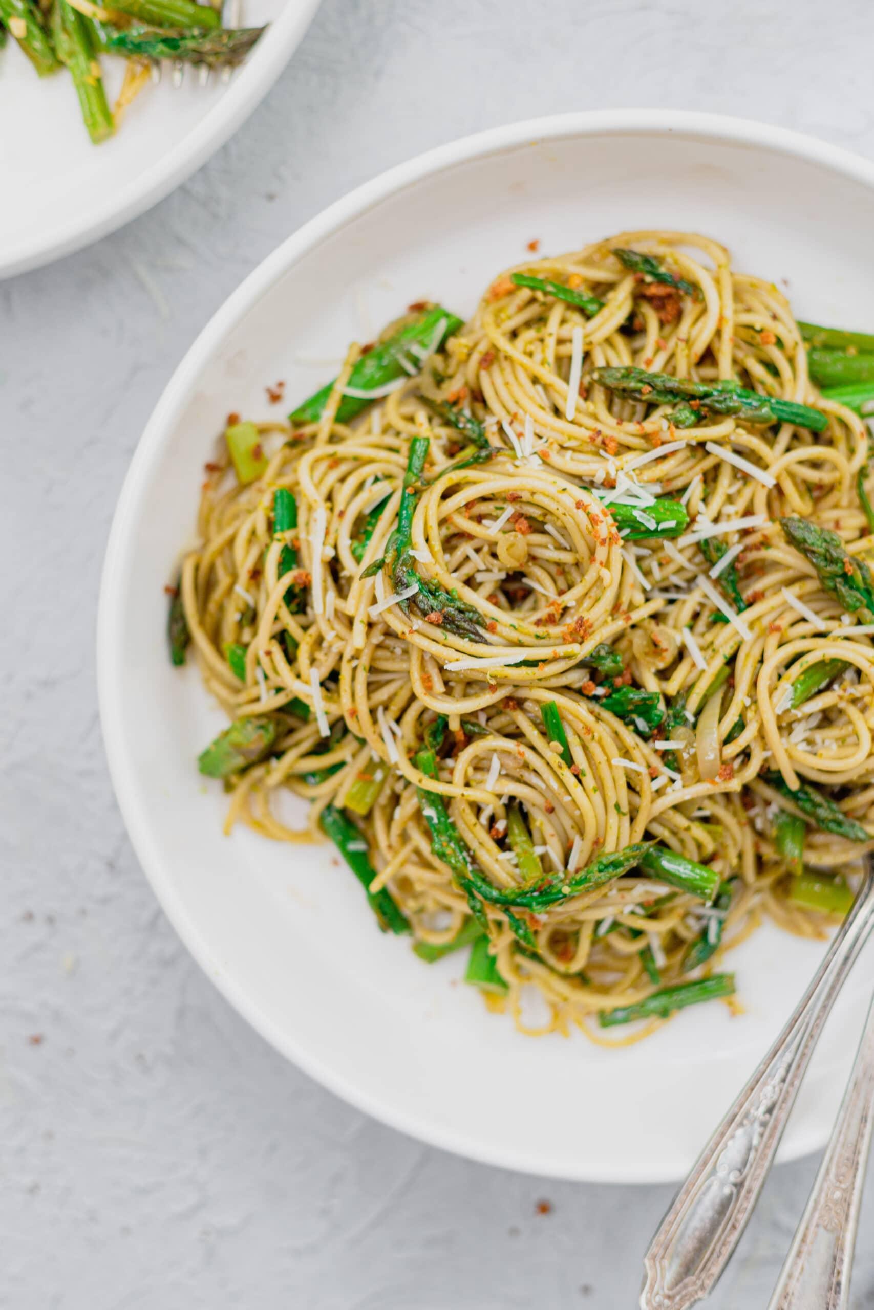 A close up of fresh asparagus pasta recipe swirled in a white bowl.