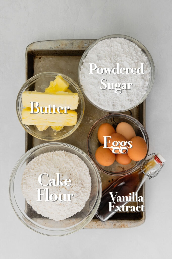 All five ingredients for a powdered sugar pound cake are in various glass bowls on a rimmed baking tray.