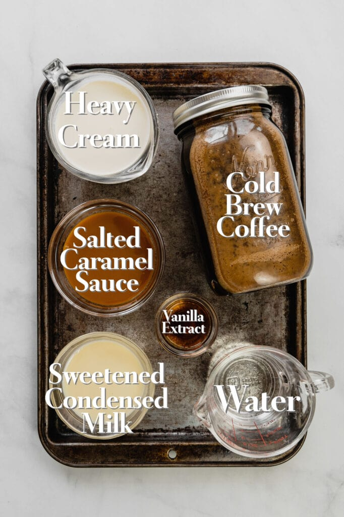 All the ingredients for the homemade salted sweet cream cold foam recipe with caramel and cold brew coffee are in various glass measuring cups and bowls on a rimmed baking sheet.
