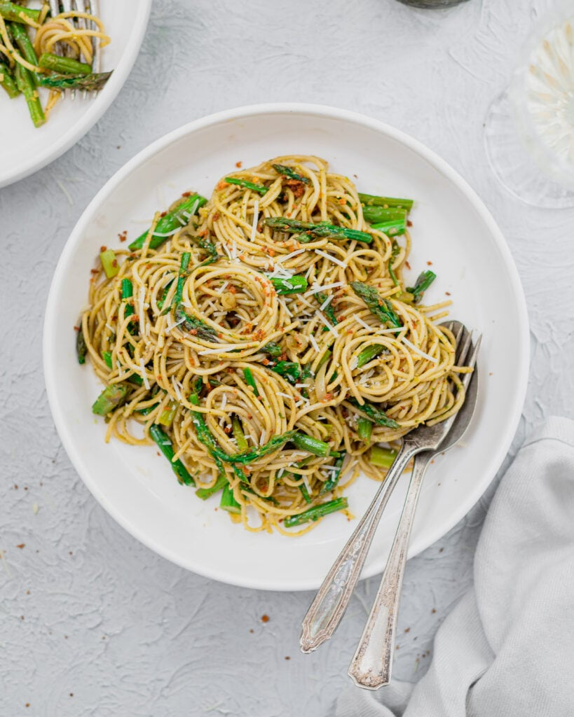 A white bowl filled with fresh asparagus pasta. There is a fork and spoon in the bowl with the pasta and a gray napkin to the side.
