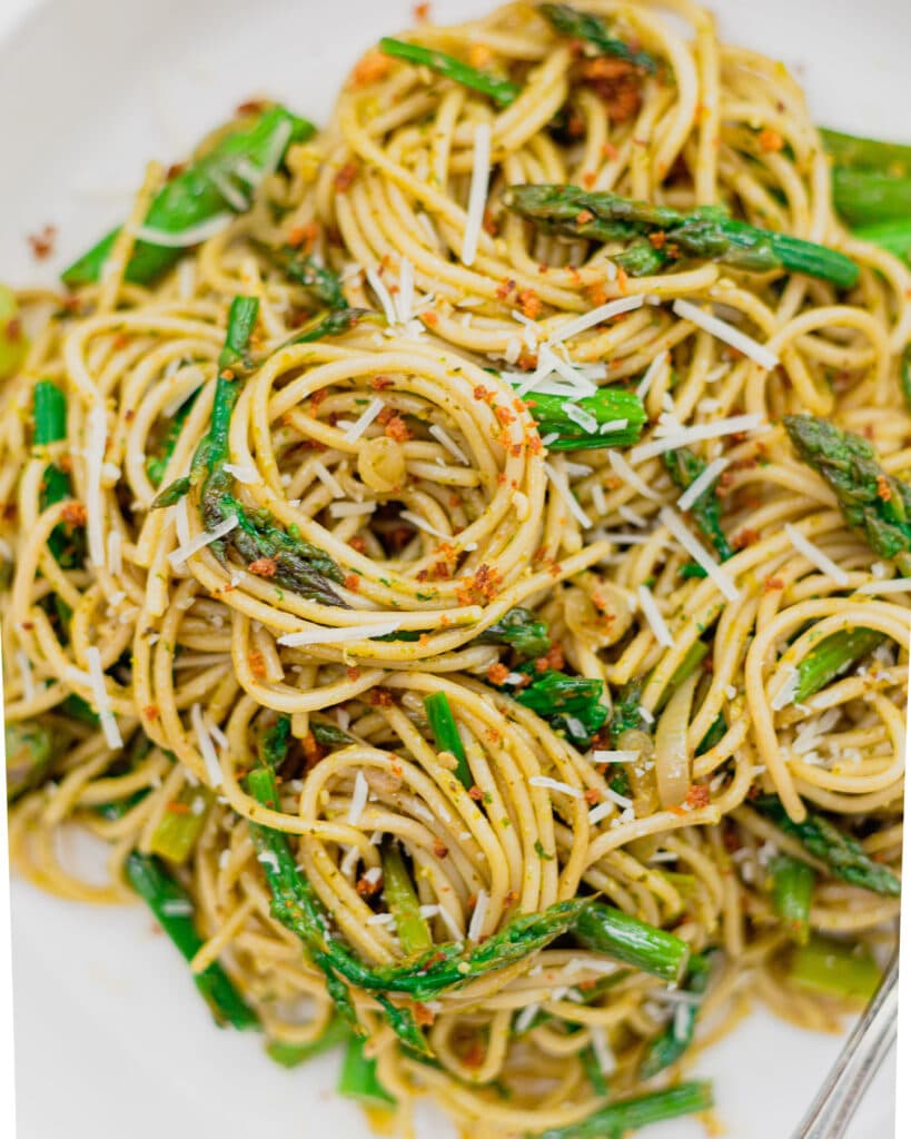 A close up of pasta with fresh asparagus, parmesan cheese, breadcrumbs, and lemon zest and red pepper flakes.