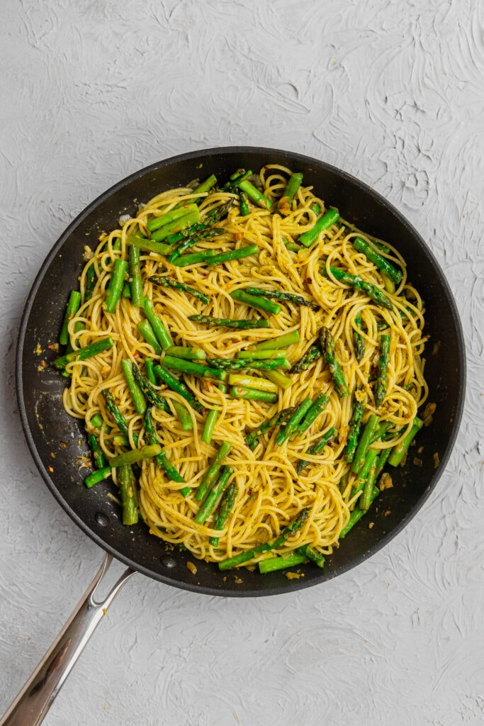 A skillet with fresh asparagus pasta.