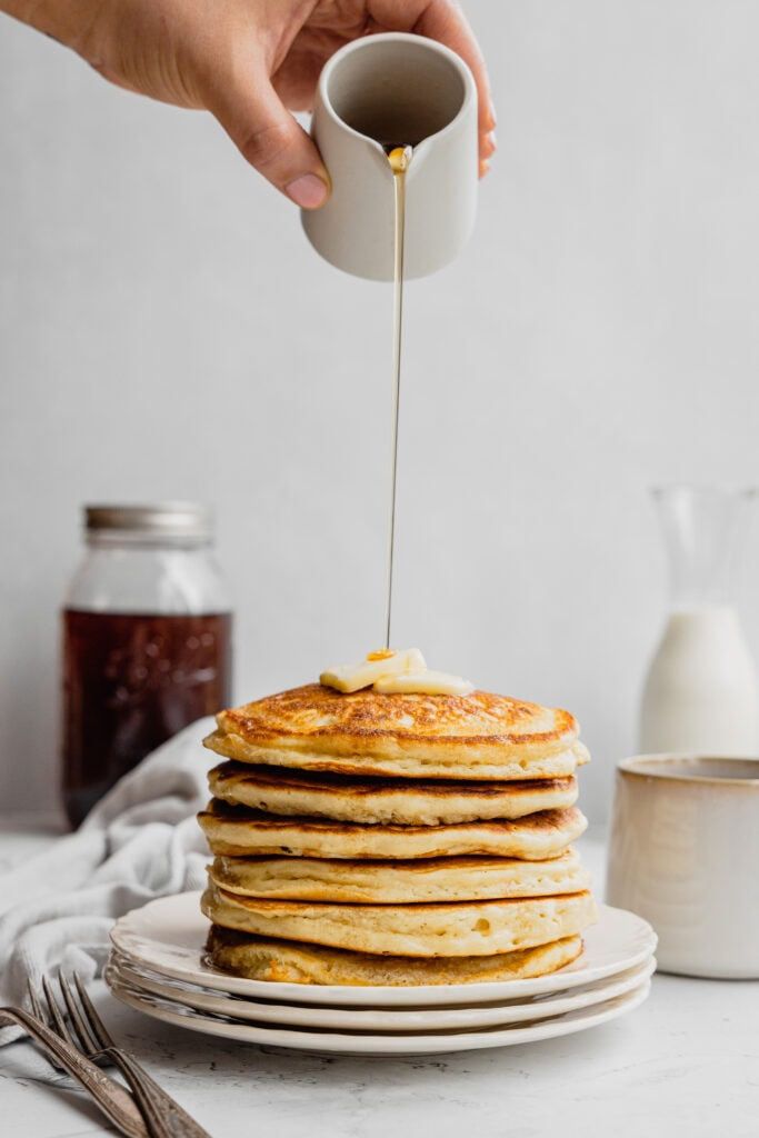 A stack of buttermilk pancakes with syrup being poured on top.