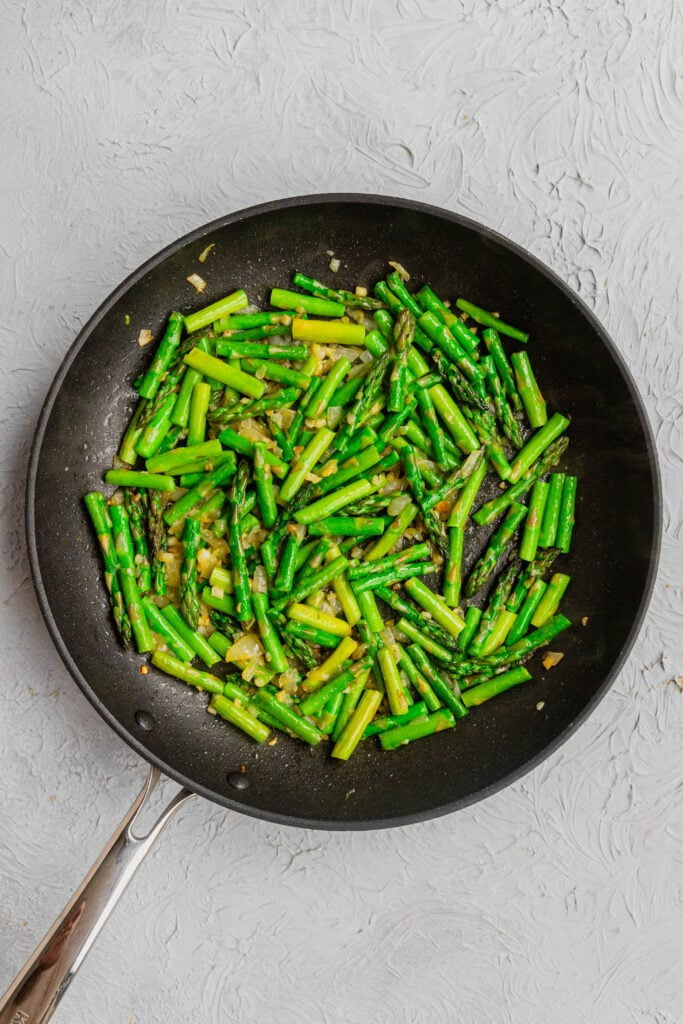 A skillet with sauteed asparagus.
