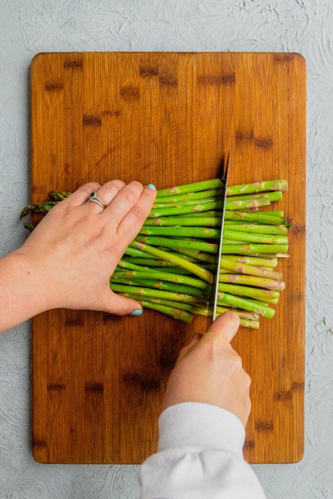 Cutting fresh asparagus stalks on a wooden cutting board.