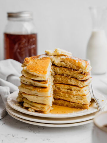 A stack of buttermilk pancakes on a white plate with a piece cut out to show the tender interior.