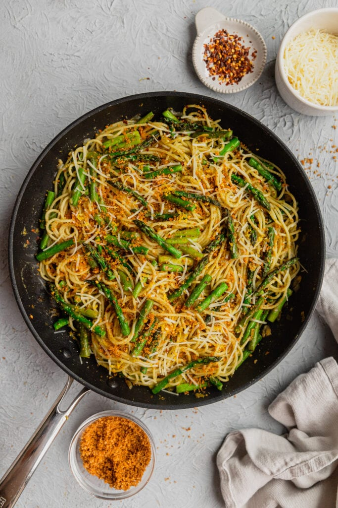 A skillet filled with an asparagus pasta recipe garnished with parmesan and breadcrumbs.