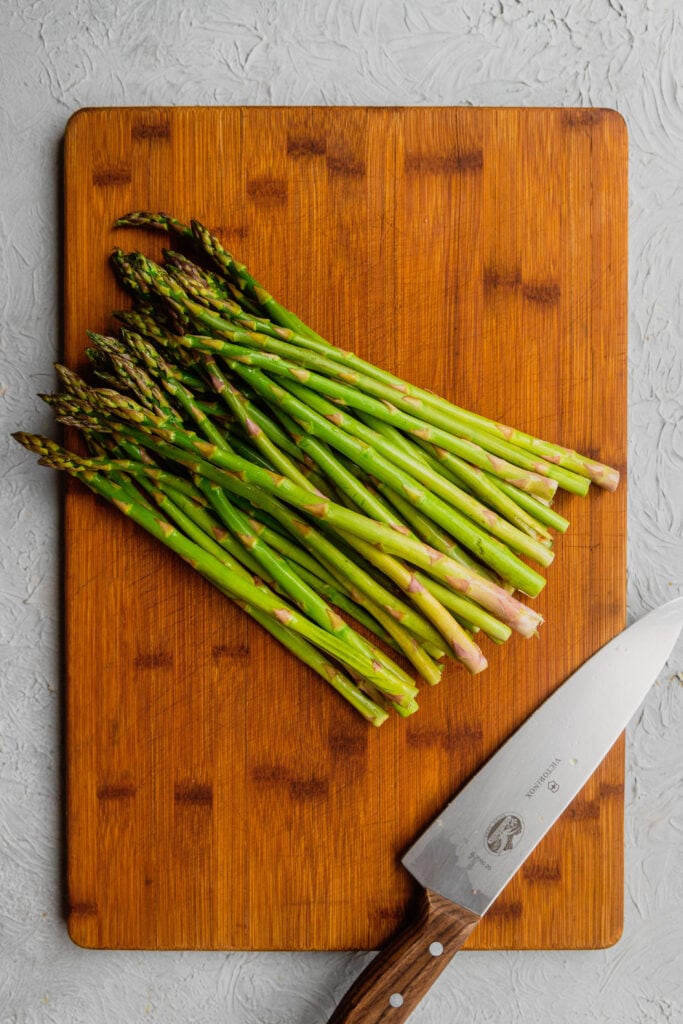 Fresh asparagus and a knife on a wooden cutting board.