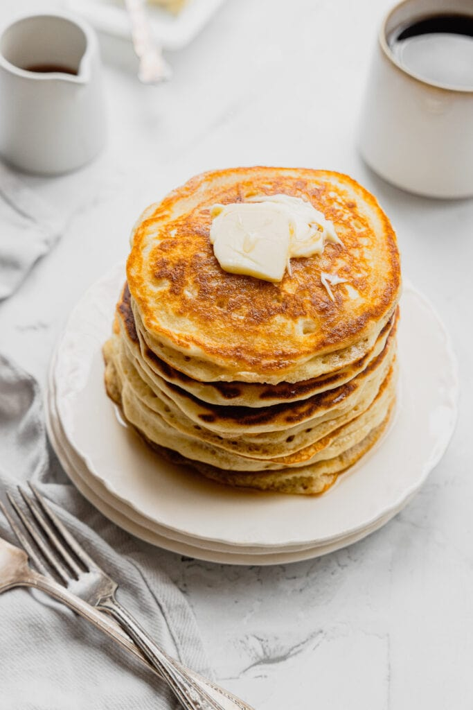 A stack of fluffy buttermilk pancakes topped with butter and syrup.
