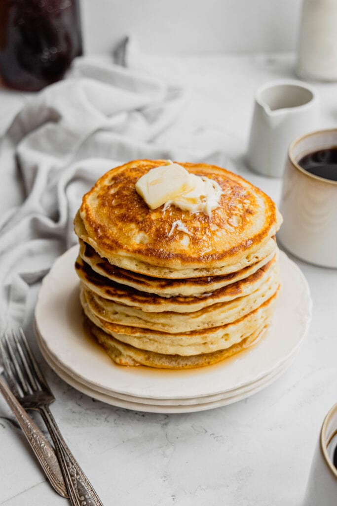 A stack of buttermilk pancakes topped with butter and maple syrup.