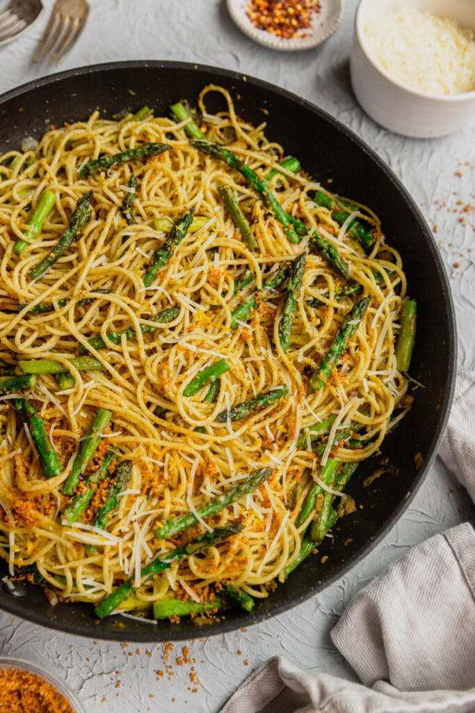 A skillet filled with a recipe for fresh asparagus pasta. The pasta is garnished with breadcrumbs and parmesan cheese, lemon zest and red pepper flakes.