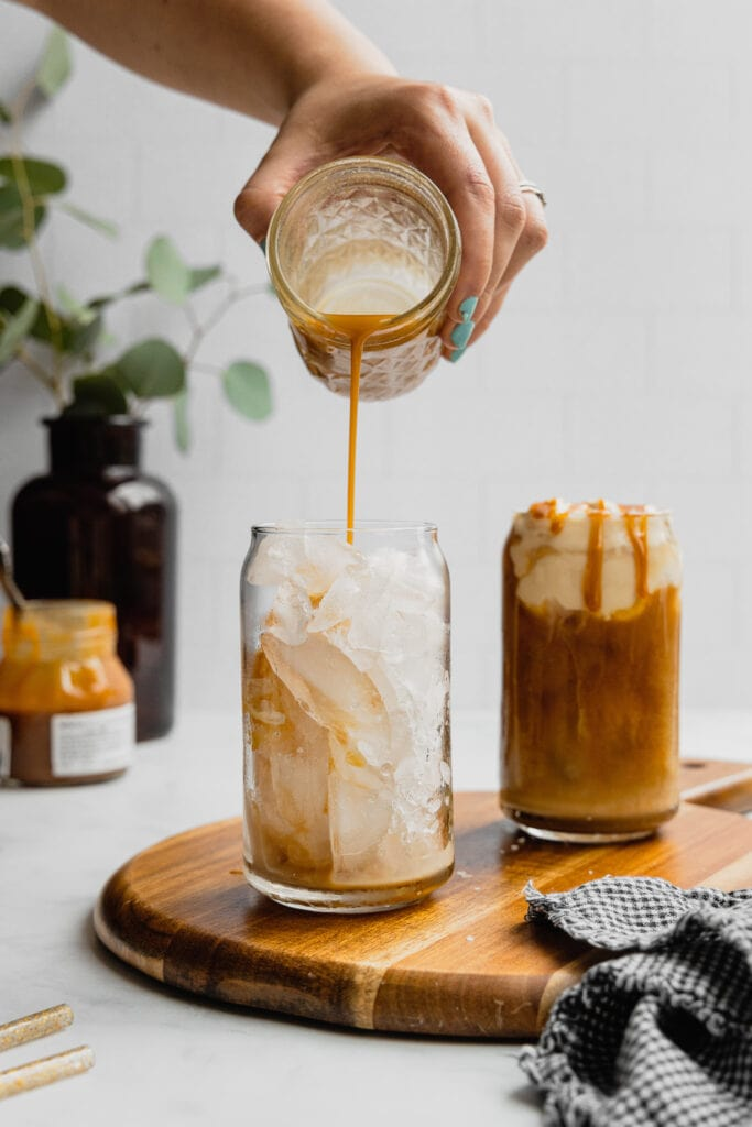 A hand pours a stream of caramel simple syrup into a glass filled with ice.