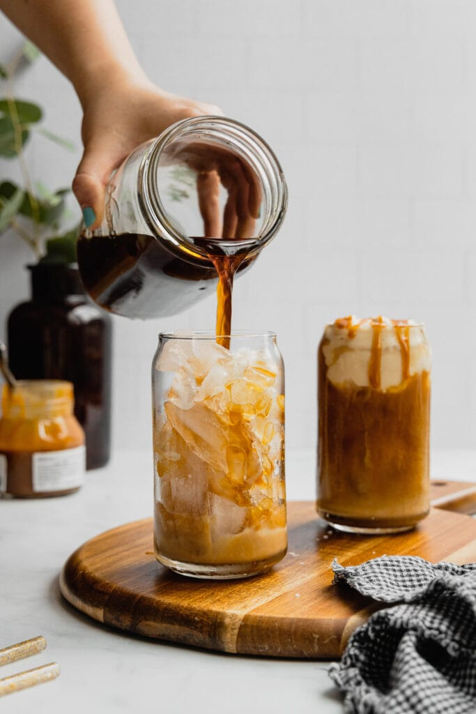 A hand pours homemade cold brew coffee into a glass filled with ice