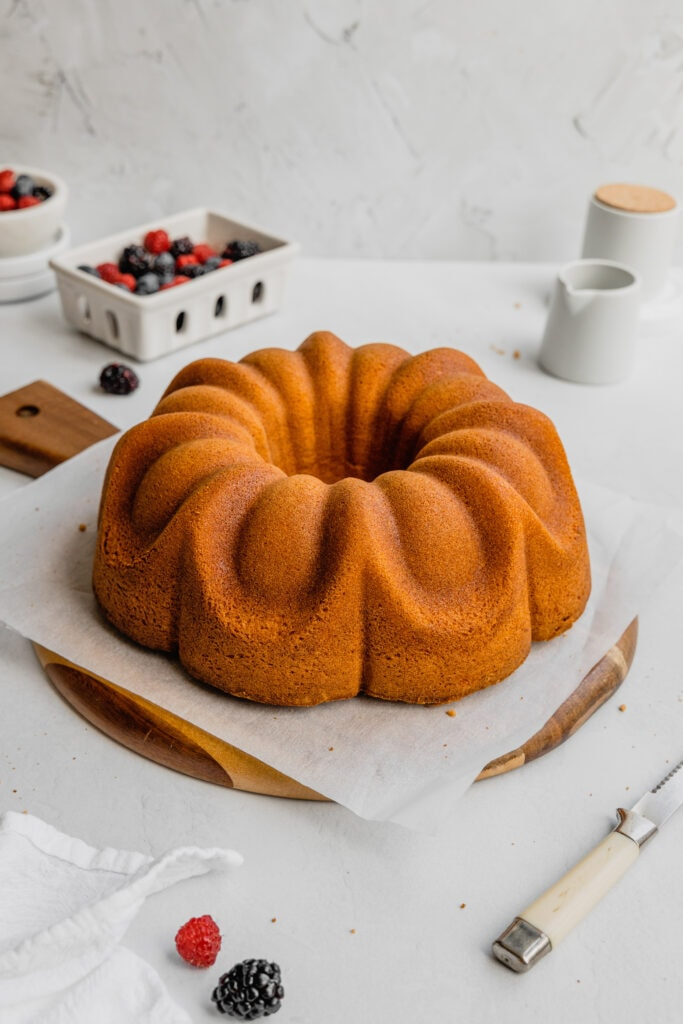 A perfectly golden powdered sugar pound cake on a piece of parchment paper on a round serving board.