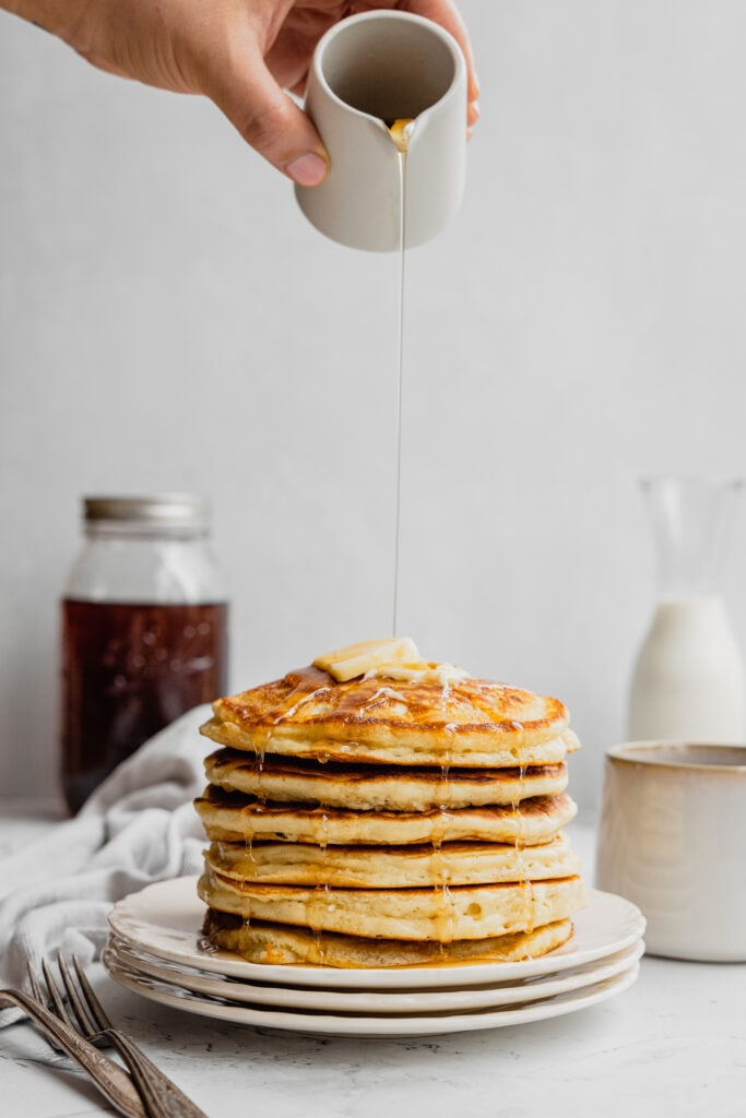 A hand holds a small creamer and pours syrup over a stack of fluffy buttermilk pancakes.