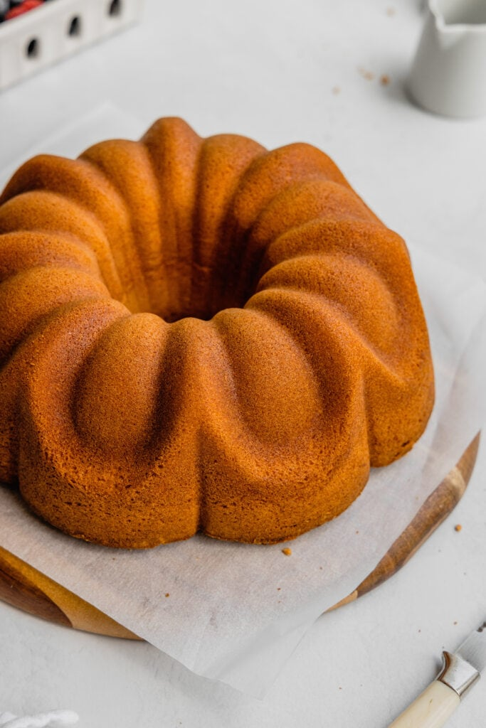Perfect bundt cake pound cake on a piece of parchment paper set over a wooden cake board.