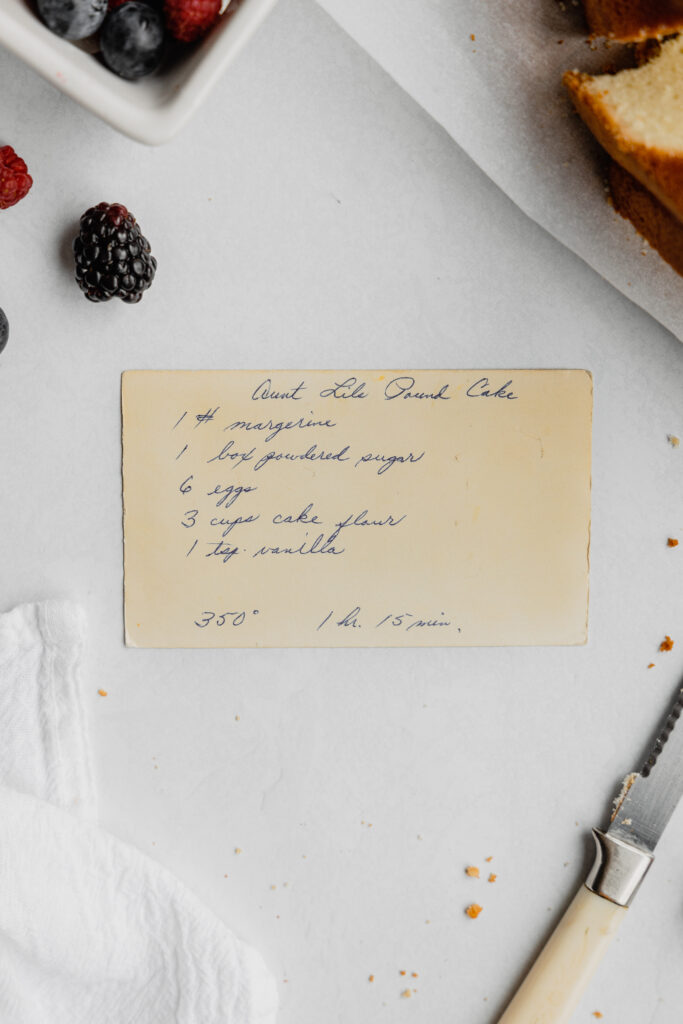 A vintage recipe card with the recipe for powdered sugar pound cake with berries and cake crumbs scattered around it.