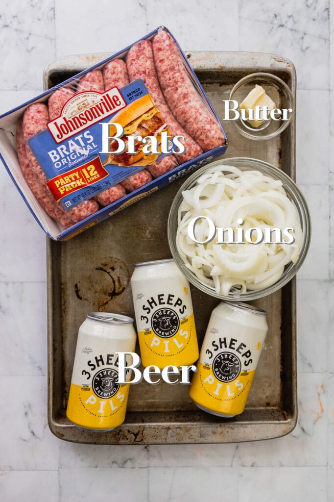 All of the ingredients for perfect beer brats and onions are laid out on a rimmed baking sheet.