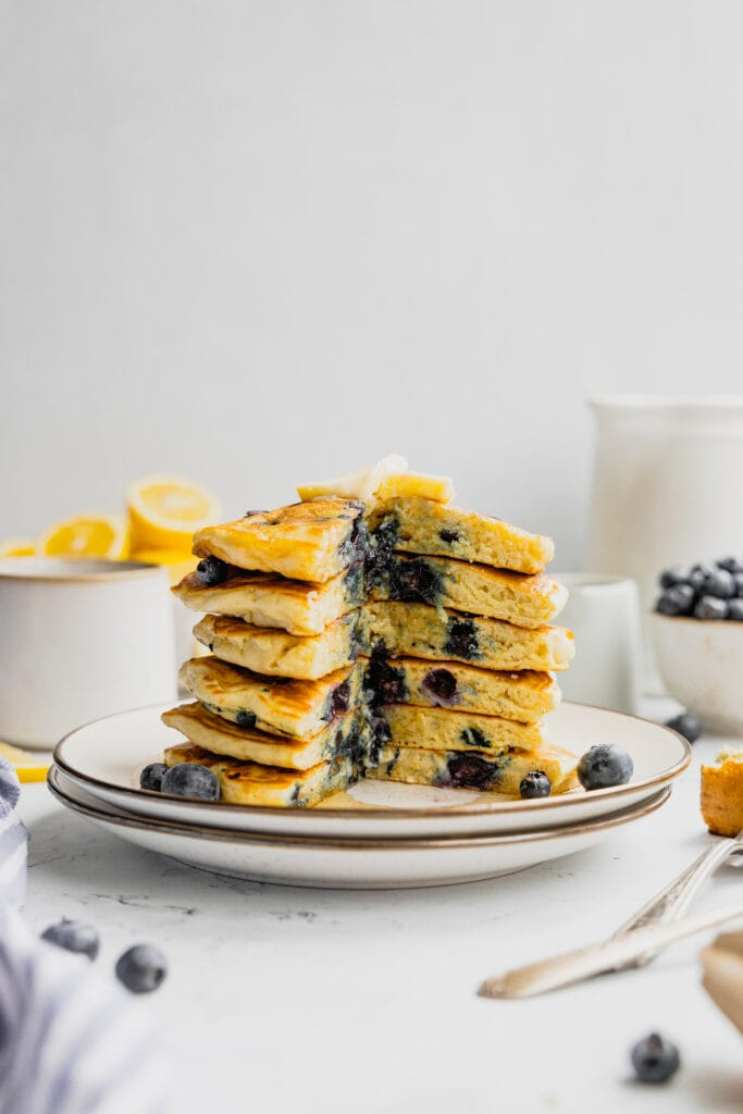 A stack of lemon blueberry pancakes on a white plate with lemon slices and fresh blueberries scattered around.