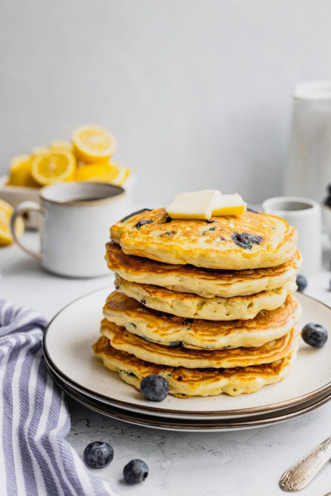 A large stack of blueberry lemon pancakes topped with butter.